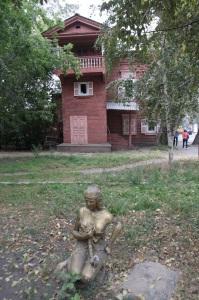 Detalle de un jardín con una casa de madera típica al fondo